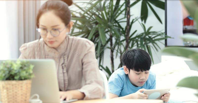 Kvinna som arbetar på bärbara datorn med pojken som spelar minnestavladatoren arkivfoto