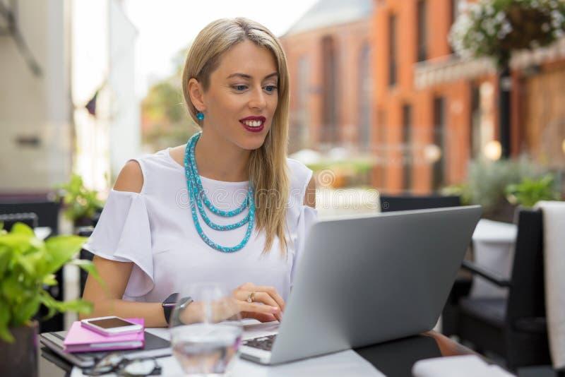 Kvinna som arbetar på bärbara datorn, medan ha kaffe i utomhus- kafé arkivbilder