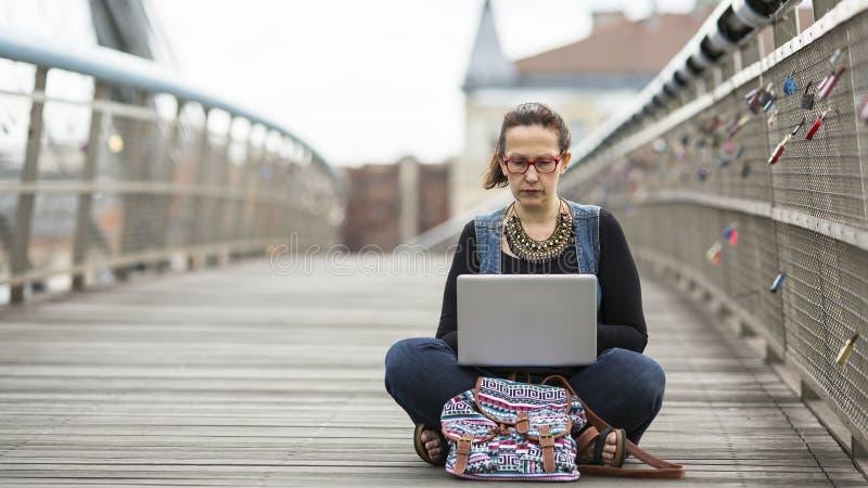 kvinna som arbetar på bärbara datorn, medan sitta på gatan Begreppet av den funktionsdugliga freelanceren eller bloggeren arkivbilder