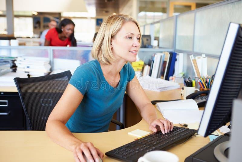 Kvinna som arbetar på datoren i modernt kontor royaltyfri fotografi