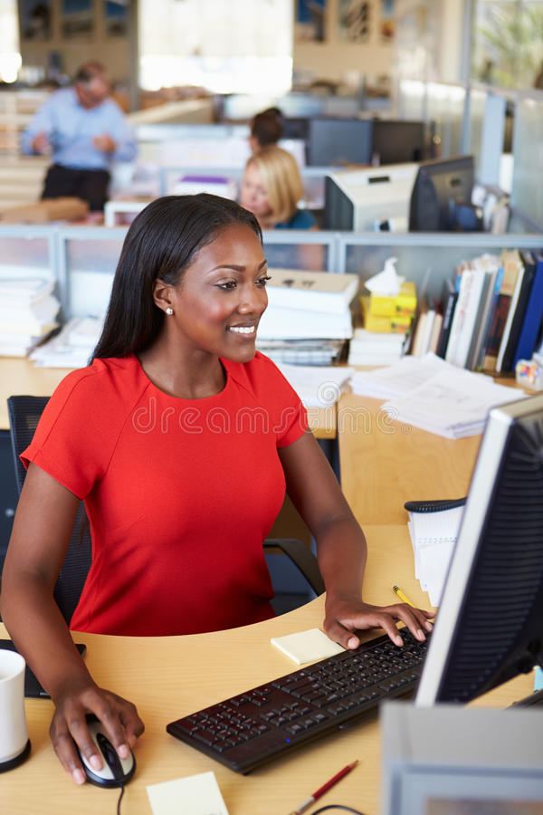 Kvinna som arbetar på datoren i modernt kontor arkivbild