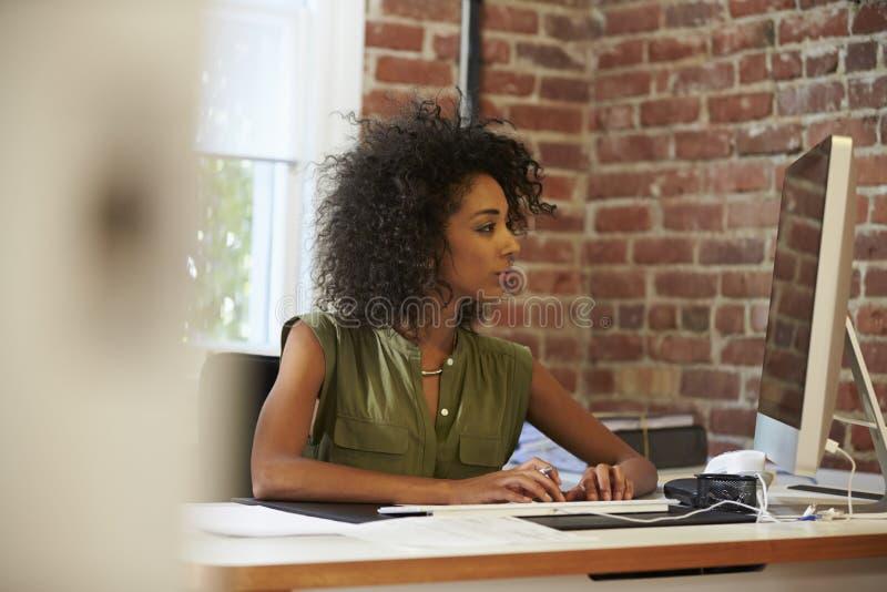 Kvinna som arbetar på datoren i modernt kontor royaltyfria foton