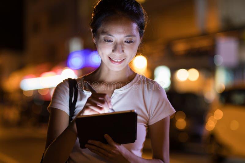 Kvinna som arbetar på den digital minnestavlan och penna i staden på natten fotografering för bildbyråer