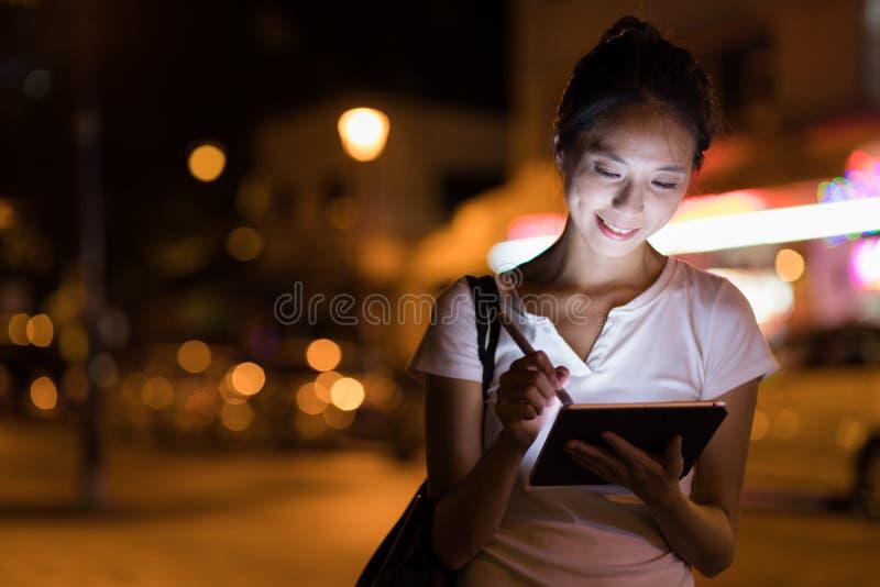 Kvinna som arbetar på den digitala minnestavlan i staden på natten arkivfoton