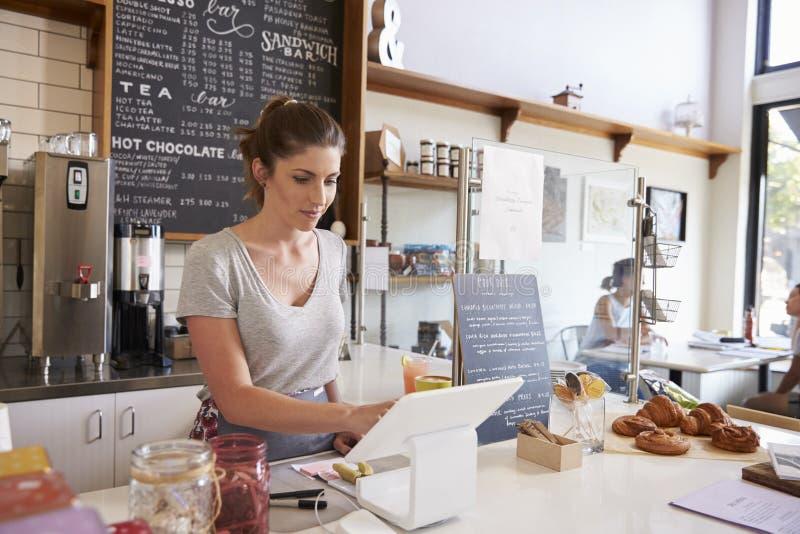 Kvinna som arbetar på kassalådan på en coffee shop, bred vinkel royaltyfria bilder