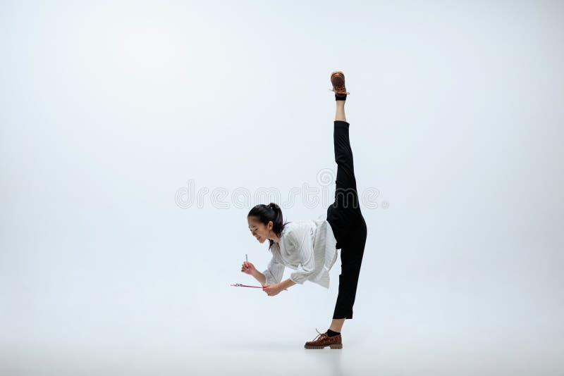 Kvinna som arbetar på kontoret, och hoppa som isoleras på studiobakgrund royaltyfri fotografi