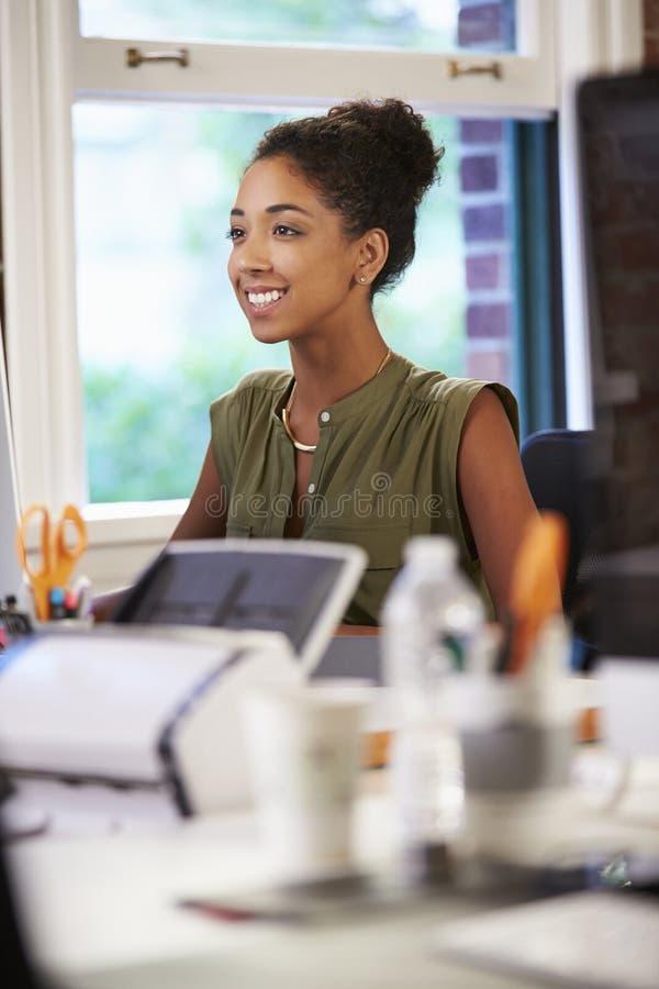 Kvinna som arbetar på skrivbordet i modernt kontor arkivbilder