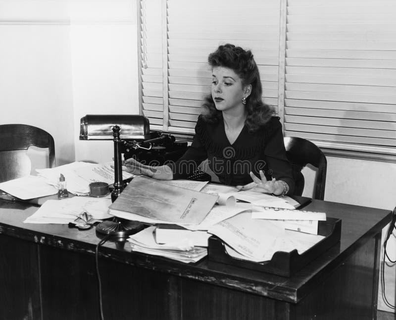 Kvinna som arbetar på skrivbordet som täckas i legitimationshandlingar (alla visade personer inte är längre uppehälle, och inget  royaltyfria bilder