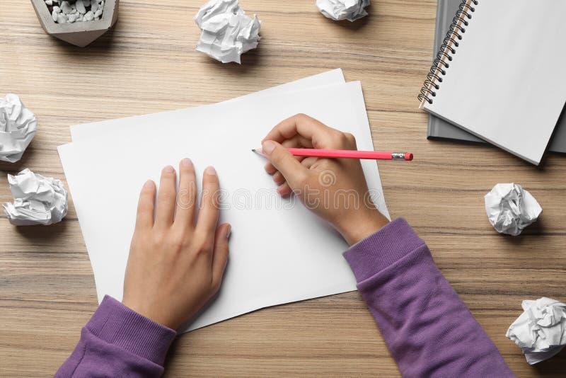 Kvinna som arbetar på tabellen med skrynkligt papper Utveckling av id? royaltyfri foto