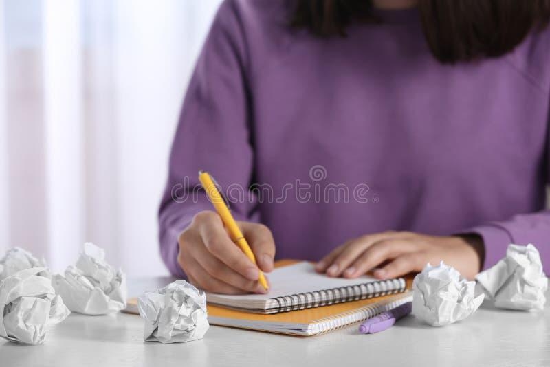 Kvinna som arbetar p? tabellen med skrynkligt papper Utveckling av id? royaltyfri foto