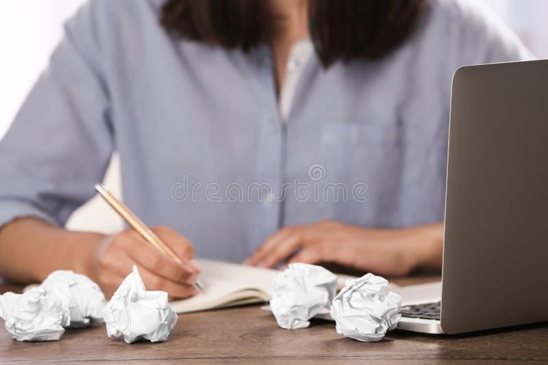 Kvinna som arbetar p? tabellen med skrynkligt papper Utveckling av id? arkivbilder