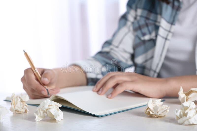 Kvinna som arbetar p? tabellen med skrynkligt papper Utveckling av id? arkivbild
