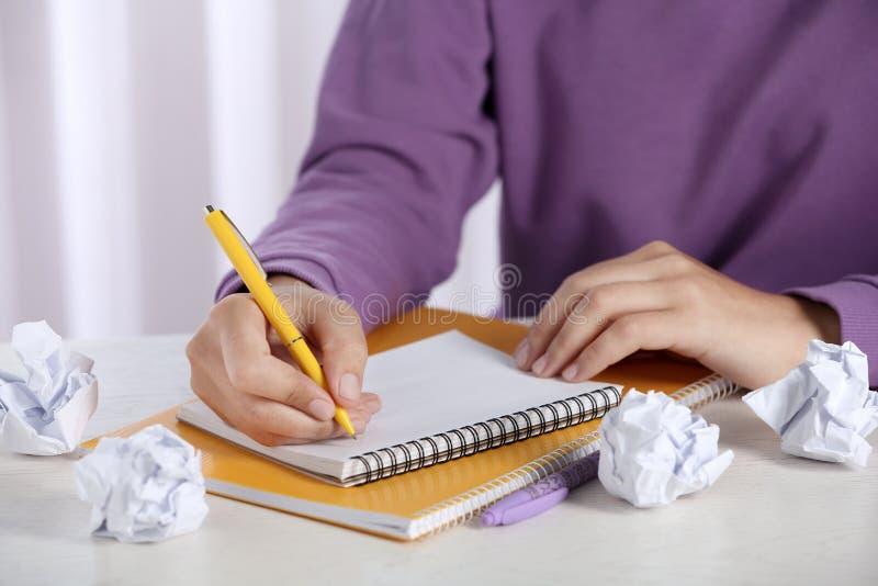 Kvinna som arbetar p? tabellen med skrynkligt papper Utveckling av id? royaltyfria bilder