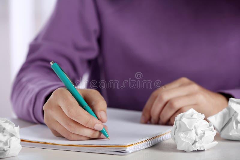 Kvinna som arbetar p? tabellen med skrynkligt papper Utveckling av id? royaltyfri bild