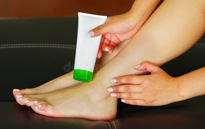 Kvinna som att bry sig om hennes fot och sätter hydratisera kräm på den med den kräm- flaskan arkivfoto