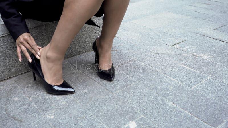 Kvinna som av tar åtsittande skor för hög häl, smärtsamt skrubbsår på fot, åderbråcks åder royaltyfria foton
