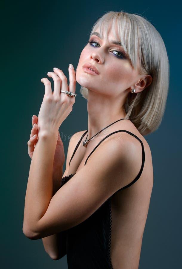 Kvinna som av visar hennes smycken i bärande tillbehör och smycken för modebegrepp som isoleras på blå mörk bakgrund arkivfoto