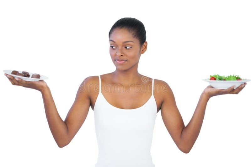 Kvinna som avgör inte att äta healthily eller arkivbilder