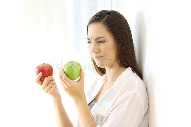 Kvinna som avgör mellan röda och gröna äpplen royaltyfria bilder