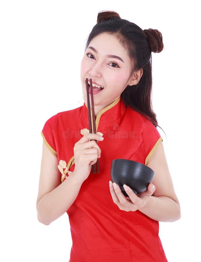 Kvinna som bär den kinesiska cheongsamklänningen med pinnar och bunke I arkivbild