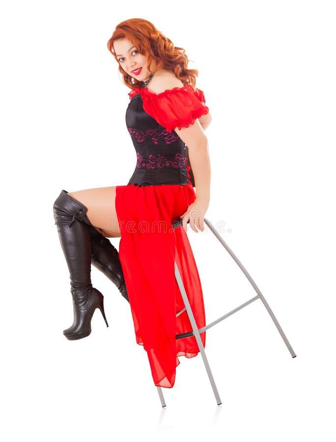 Kvinna som bär den röda kappan och kängor på stol royaltyfri bild