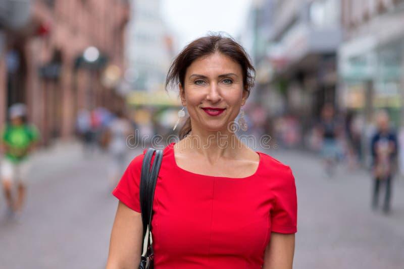 Kvinna som bär den röda klänningen och promenerar vägen royaltyfria bilder