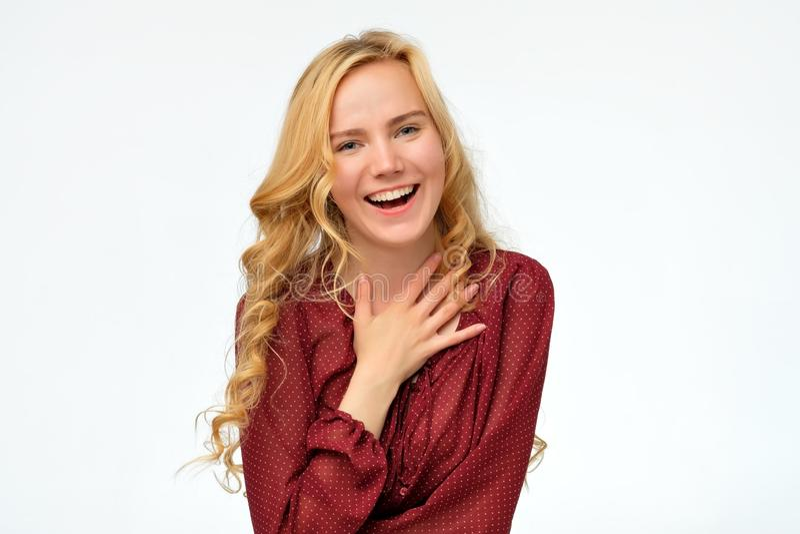 Kvinna som bär den röda skjortan som skrattar i huvudsak glat att motta komplimang arkivbild