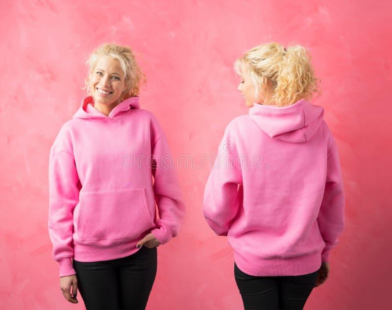 Kvinna som bär den rosa hoodien, mall för promotryckdesign royaltyfri foto