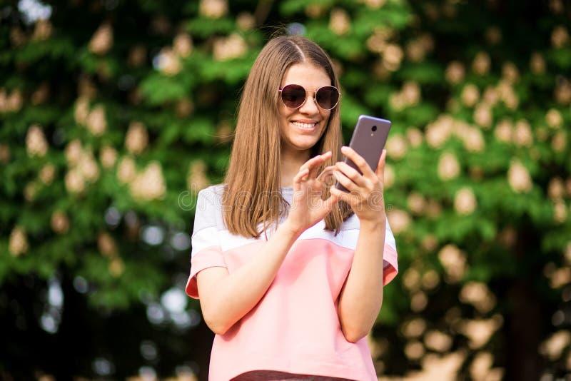 Kvinna som bär den rosa skjortan som smsar på den smarta telefonen som går i gatan royaltyfri foto