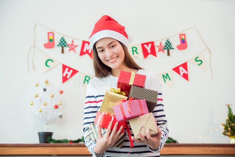 Kvinna som bär den Santa Claus hatten och innehavjulgåvan royaltyfri fotografi