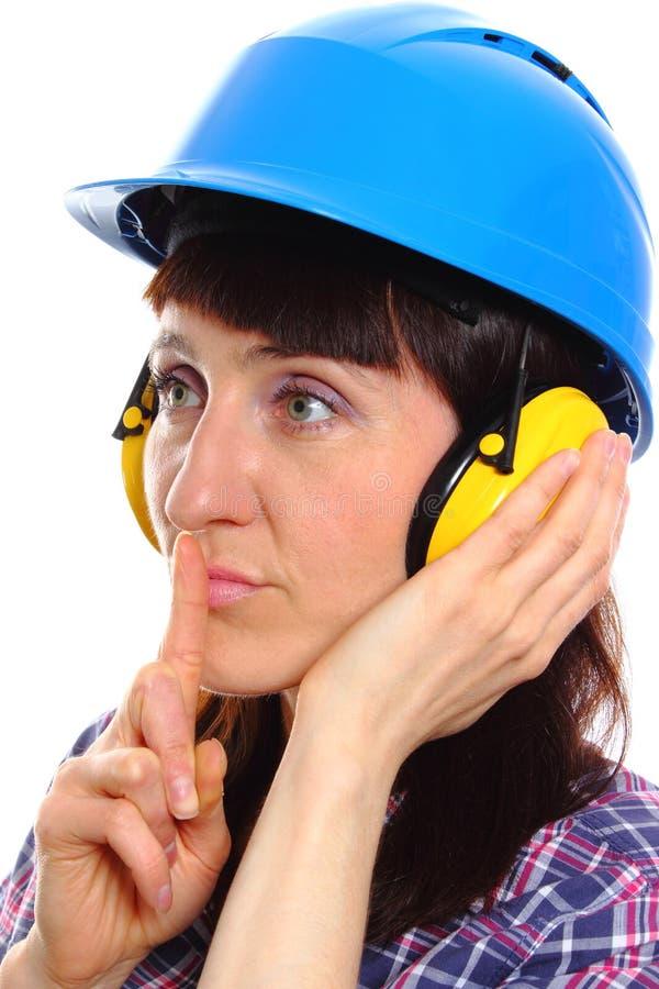 Kvinna som bär den skyddande hjälmen och hörlurar, tystnadtecken arkivbilder