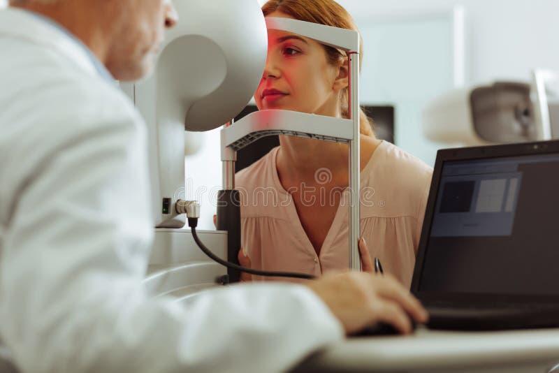 Kvinna som bär den stilfulla blusen som har konsultation av ögondoktorn arkivfoton