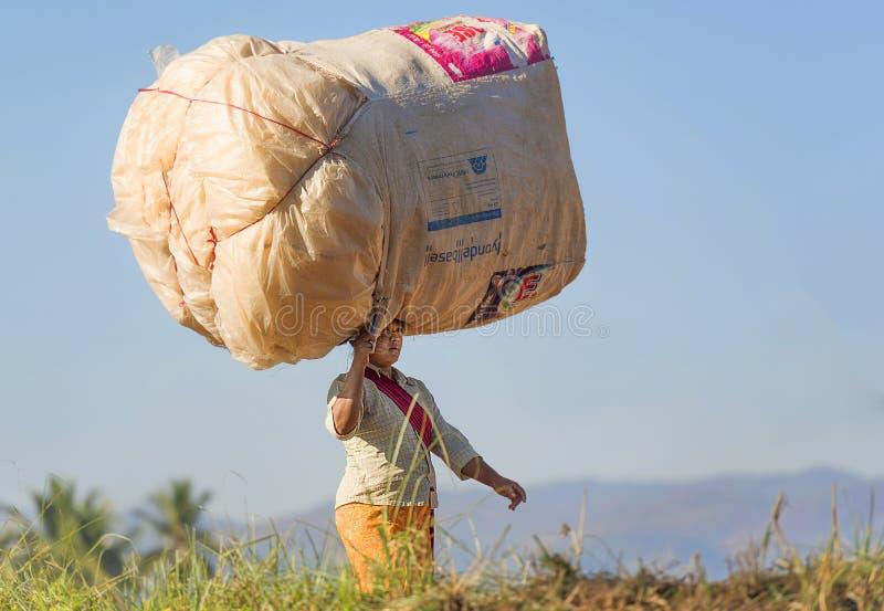 Kvinna som bär den stora påfyllningen på hennes huvud som går, i sparat, Inle Myanmar arkivbild
