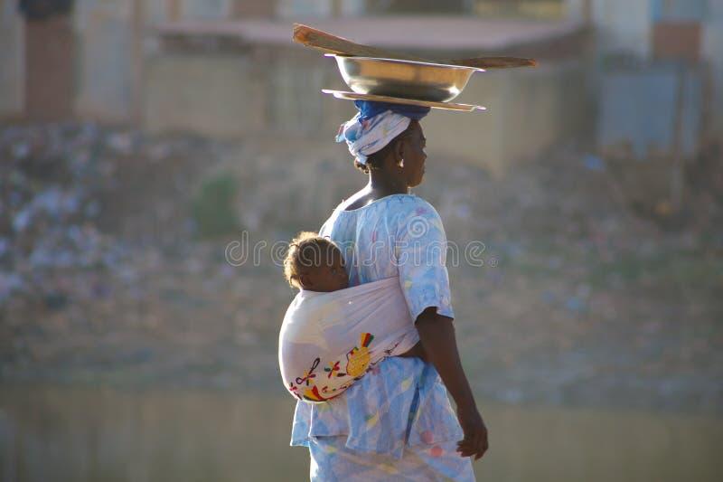 Kvinna som bär en behandla som ett barn i Mopti arkivfoto