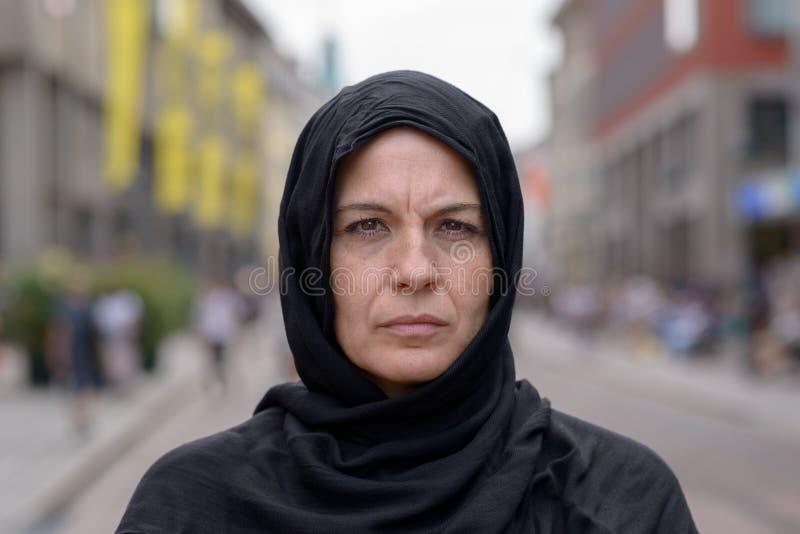 Kvinna som bär en head halsduk i en stads- gata arkivfoton