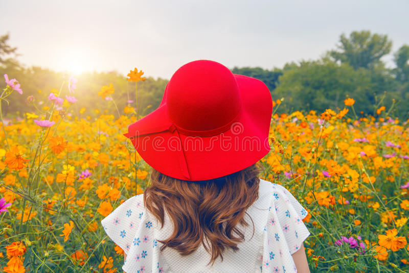 Kvinna som bär en röd hatt i ett fält av blommor arkivfoto