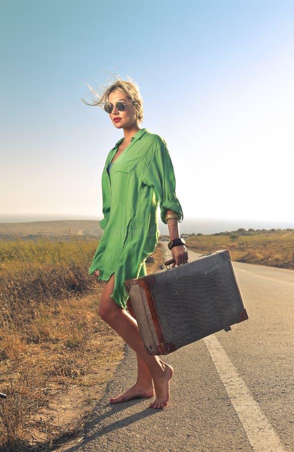 Kvinna som bär en resväska royaltyfri fotografi
