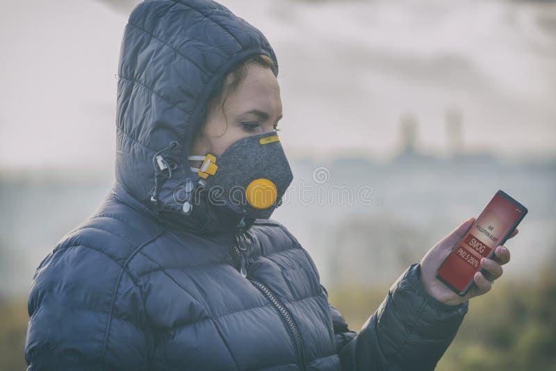 Kvinna som bär en verklig anti--smog framsidamaskering och kontrollerar aktuell luftförorening med den smarta telefonappen arkivbild