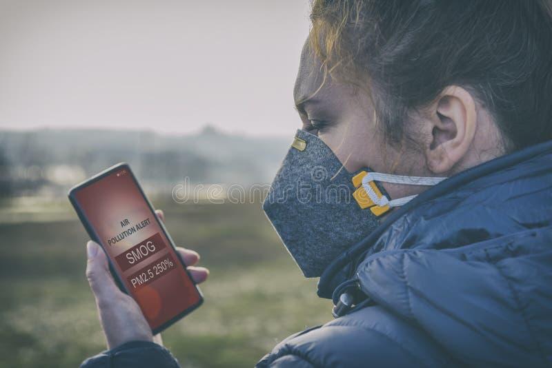 Kvinna som bär en verklig anti--smog framsidamaskering och kontrollerar aktuell luftförorening med den smarta telefonappen royaltyfri foto