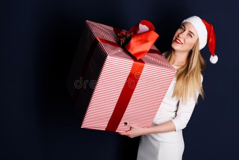 Kvinna som bär gåvor för jul för santa hatt hållande royaltyfri fotografi