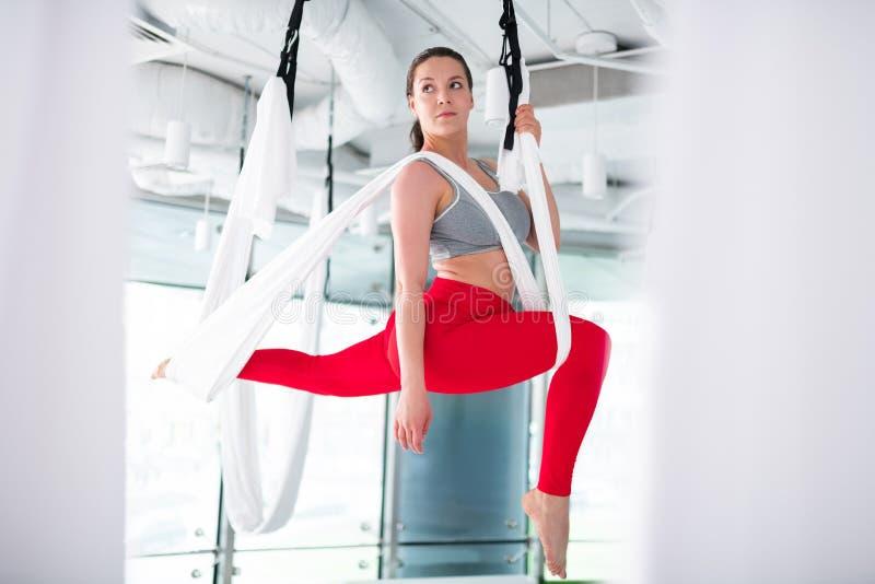 Kvinna som bär grå spännande överkantkänsla göra flyg- yoga royaltyfri fotografi