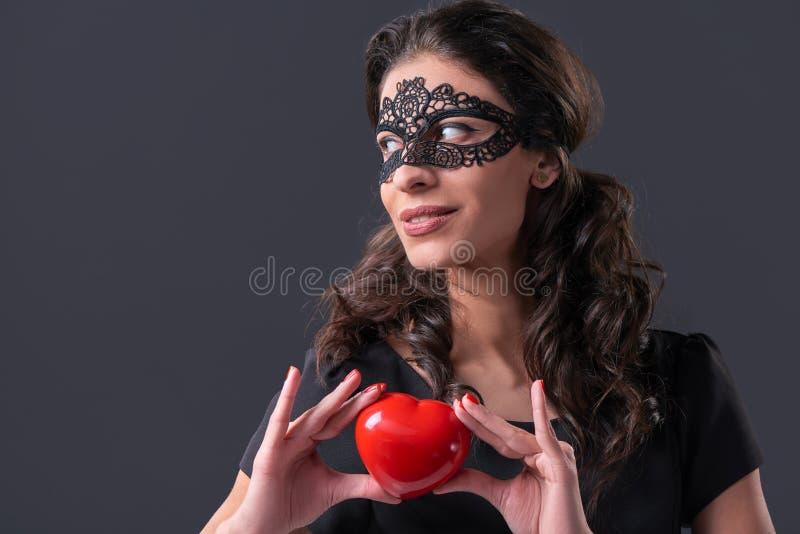 Kvinna som bär hållande hjärtaform för svart maskering royaltyfria foton