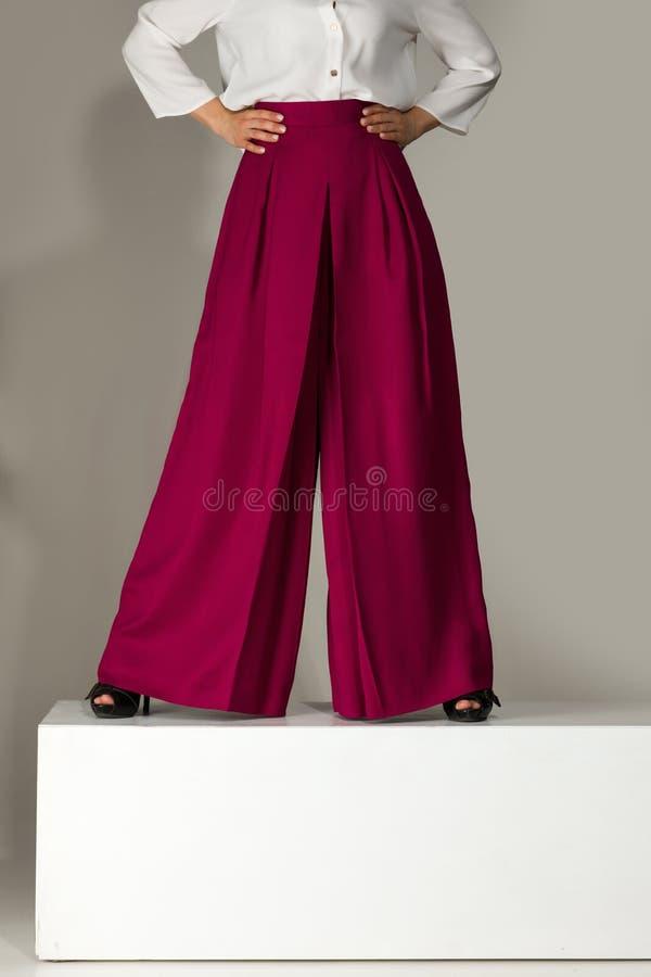Kvinna som bär höga heeled skor i burgundy byxa fotografering för bildbyråer