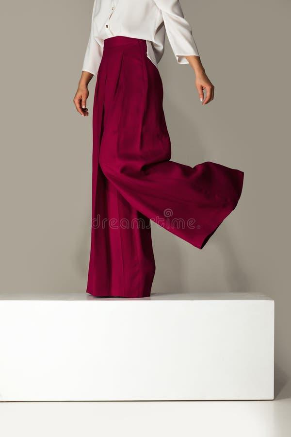 Kvinna som bär höga heeled skor i burgundy byxa royaltyfri bild