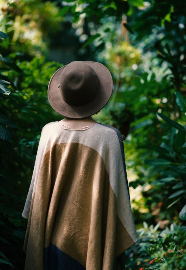 Kvinna som bär i hatt och poncho arkivfoton