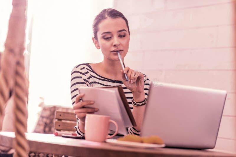 Kvinna som bär pennan och anteckningsboken för innehav för känsla för randig skjorta den fundersamma royaltyfri foto