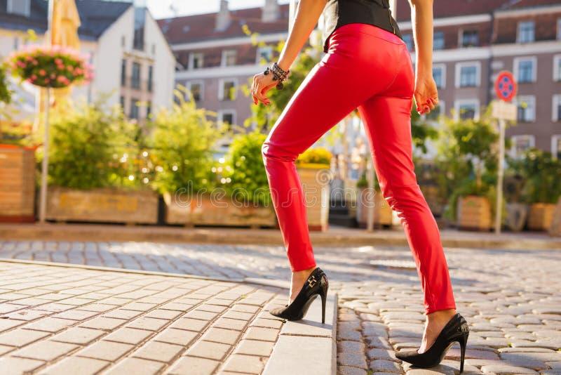 Kvinna som bär röd läderbyxa och svarta skor för hög häl royaltyfri foto