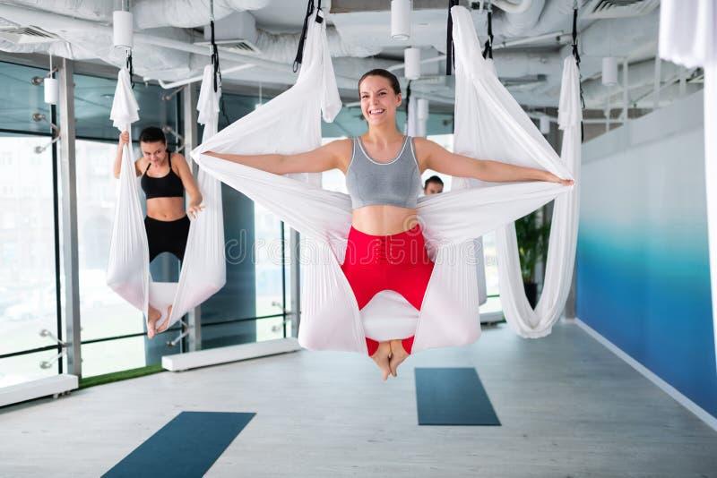 Kvinna som bär röd spännande försökande flyg- yoga för damasker känsla royaltyfri fotografi