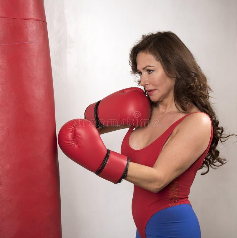 Kvinna som bär röda boxninghandskar som stansar en påse royaltyfria foton