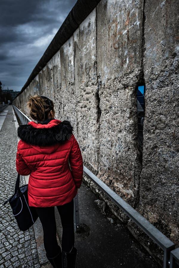 Kvinna som bär röda omslagsbesökrest av Berlin Wall arkivbilder